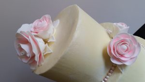 Close up of roses on 3-tier wedding cake.